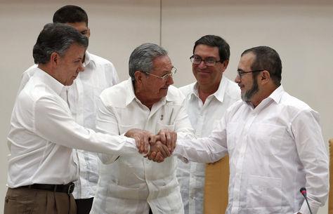 """El presidente de Colombia Juan Manuel Santos (i), el presidente de Cuba Raúl Castro (c) y el máximo líder de las FARC, Rodrigo Londoño (d), alias """"Timochenko"""", se dan la mano, durante un acto en La Habana (Cuba)."""