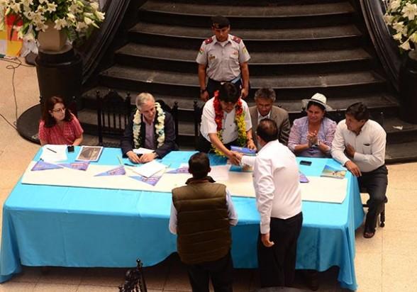 El representante de JOCA Bolivia y el Ministro de Obras Públicas saludan al presidente Evo Morales, el 12 de septiembre, en la firma del contrato. - Daniel  James Los Tiempos