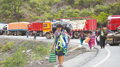 Perjuicios. Viajeros se ven obligados a caminar en uno de los puntos de bloqueo en el departamento de Chuquisaca. Foto: APG