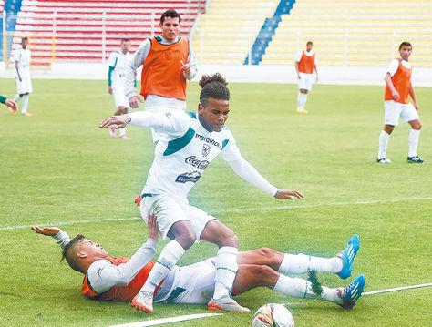 fútbol. Jorge Cuéllar se tira al piso en procura de frenar a Leonel Morales en la práctica de ayer. Foto: Ángel Illanes