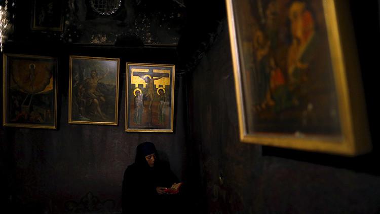 Un devoto reza en la cueva debajo de la Basílica de la Natividad, Belén