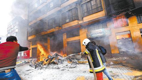 Documentos. Bomberos y ciudadanos apagan las fogatas en el ingreso al edificio municipal de El Alto, donde se encuentran cenizas de documentos y muebles.