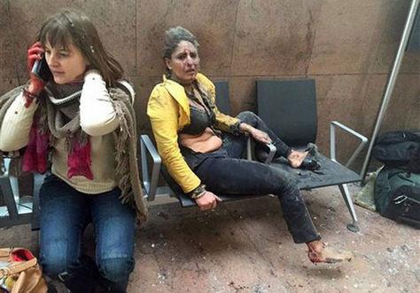 Nidhi Chaphekar, de chaqueta amarilla, aparece cubierta de polvo tras un ataque terrorista en Bruselas. En medio del caos, una mujer habla por su teléfono celular.