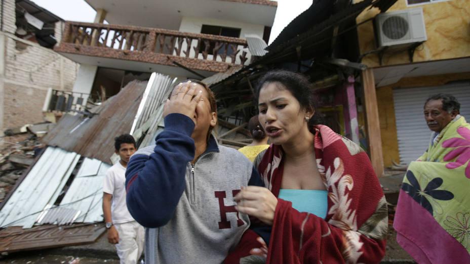 Una mujer llora mientras se encuentra junto a la casa destruida por el terremoto en la ciudad costera del Pacífico de Pedernales, Ecuador.