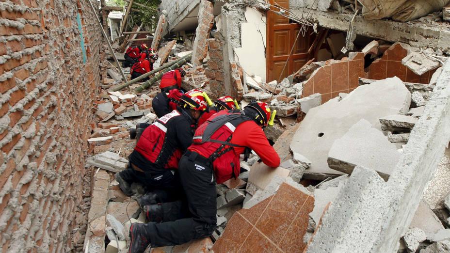 Bomberos supervisan los escombros de una vivienda en búsqueda de sobrevivientes. AP