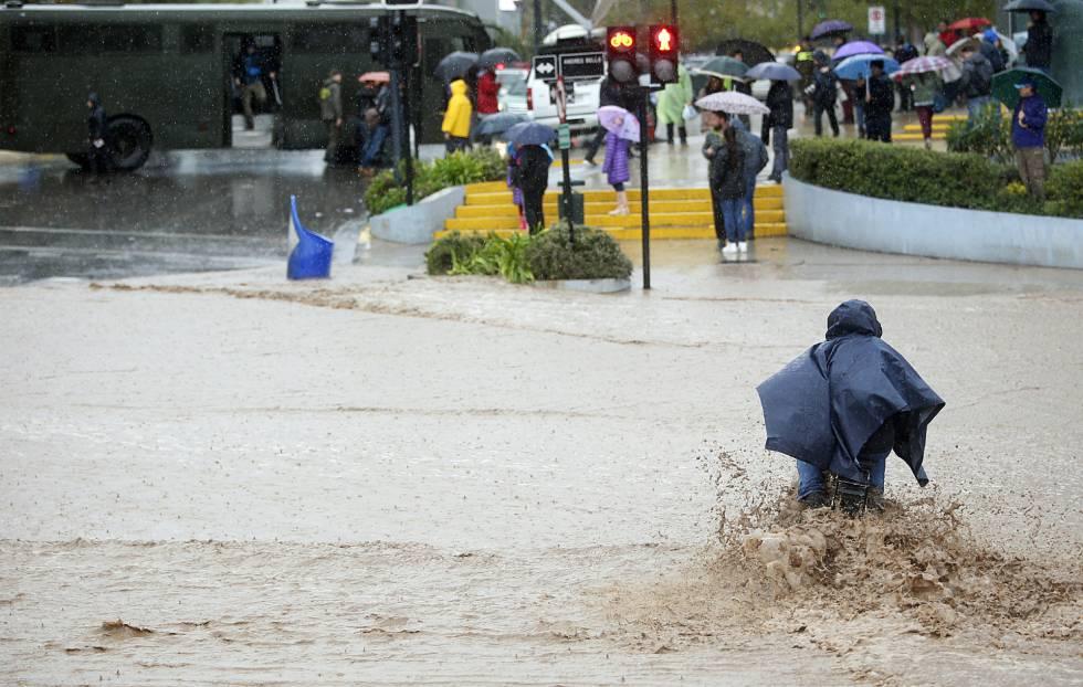 Un hombre cruza una calle inundada en Santiago de Chile.