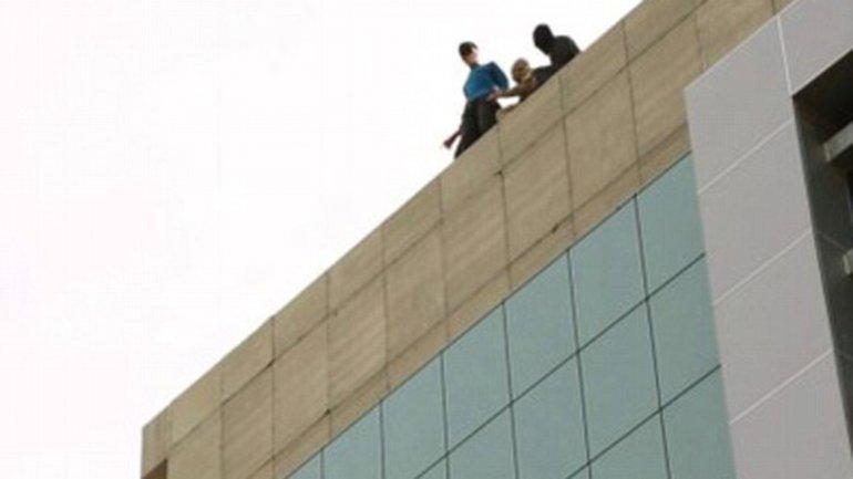 La víctima, en el borde del edificio, es rodeada por terroristas del Estado Islámico