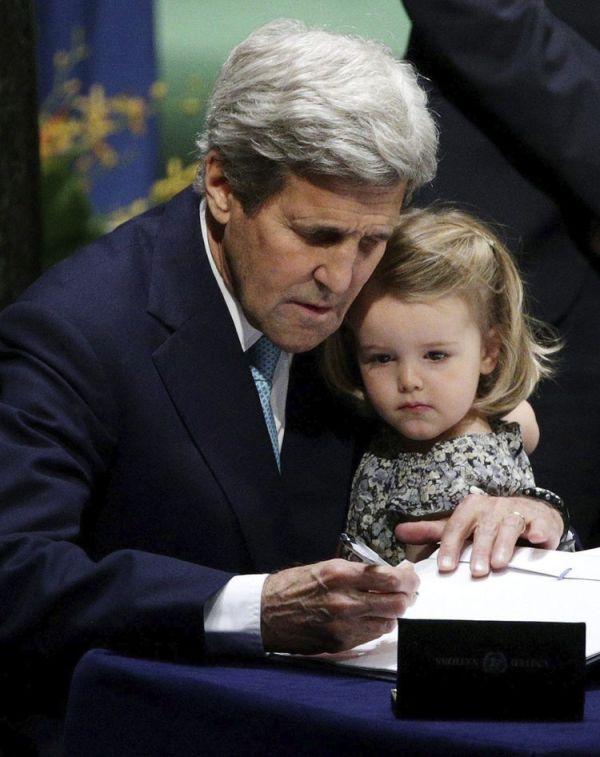 El secretario de Estado de EE.UU., John Kerry (i), sostiene a su nieta, Isabelle Dobbs-Higginson, mientras firma el Acuerdo de París en la sede de la Naciones Unidas de Nueva York (EE.UU.)
