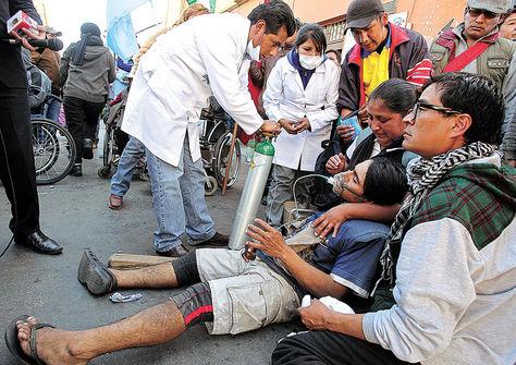 Auxilio. Wilson Irahola, persona con discapacidad que cargó una cruz, recibe oxígeno tras aspirar el gas pimienta.