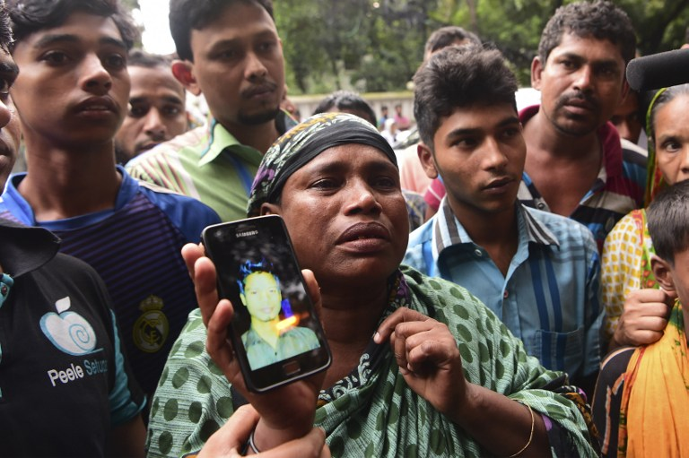 "A Bangladeshi woman holds a photograph of her son, who worked at a cafe that was the scene of an attack and seige, and who is missing, in Dhaka on July 3, 2016. Bangladesh said July 3 the attackers who slaughtered 20 hostages at a restaurant were well-educated followers of a homegrown militant outfit who found extremism ""fashionable"", denying links to the Islamic State group. As the country held services to mourn the victims of the siege in Dhaka, details emerged of how the attackers spared the lives of Muslims while herding foreigners to their deaths. / AFP PHOTO / APF / STR"
