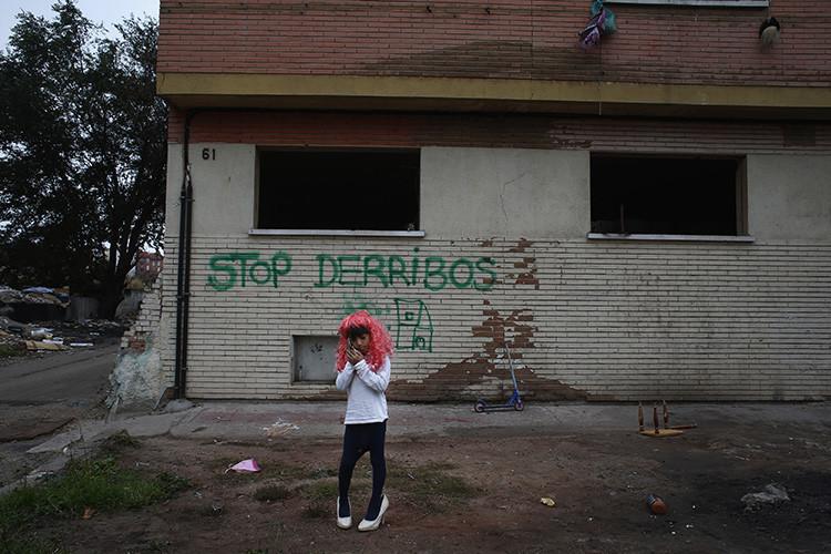 Un niño de 7 años frente a la antigua fábrica donde vive con su familia después de que se decidiera la demolición de su vivienda en Madrid (España)