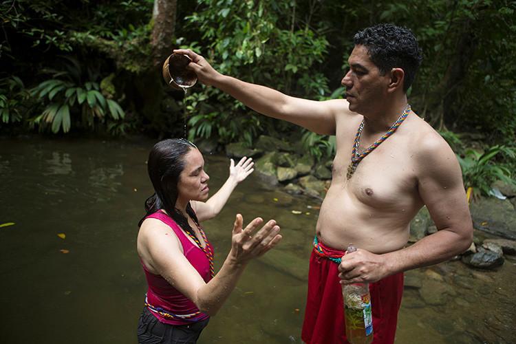 Una mujer recibe un baño de purificación en el pozo de San Juan del Dinero, en la montaña de Sorte en las afueras de Chivacoa , en el estado de Yaracuy , Venezuela