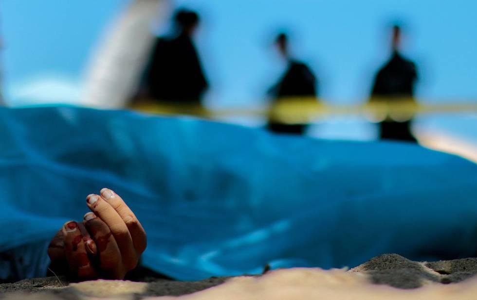 Forenses observan el cuerpo de un hombre en Acapulco, en julio de 2016.