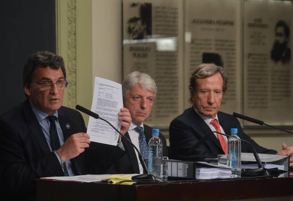 El secretario de derechos humanos argentino, Claudio Avruj, muestra un informe desclasificado junto al vicecanciller, Carlos Foradori, y el representante especial para los derechos humanos de la Cancillería, Leandro Despouy (dcha).