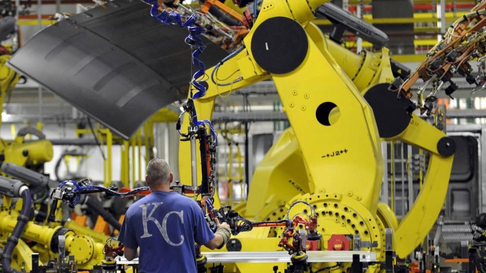 Foto: Un empleado y un robot, en la fábrica de Ford en la ciudad de Kansas.