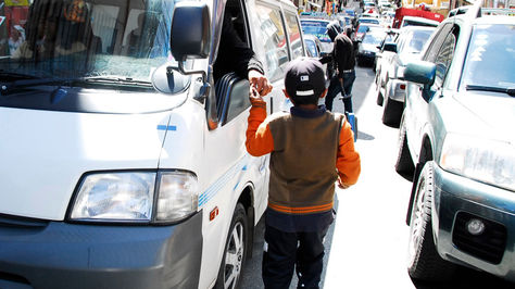 Un niño trabaja limpiando los parabrisas de los vehículos en el centro de la ciudad de La Paz. Foto: Miguel Carrasco-archivo
