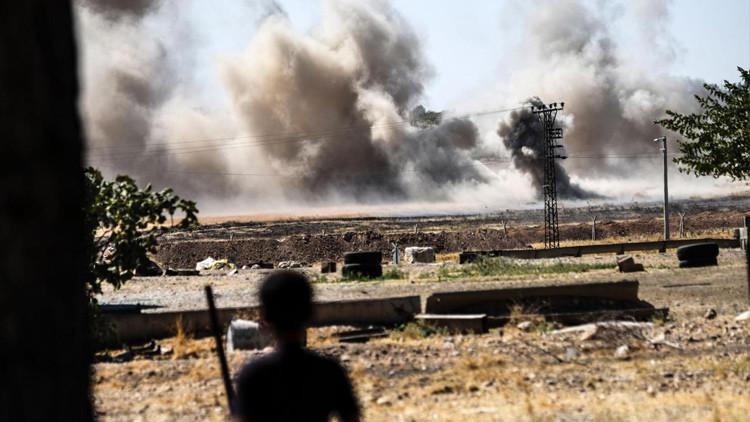 Un niño observa desde la localidad de Karkemish, situada en la frontera turco-siria, cómo el humo cubre Yarábulus (Siria), el 1 de septiembre de 2016.