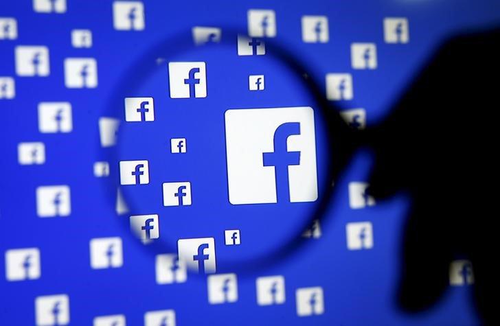 Un hombre con una lupa frente al logo de Facebook. Foto: REUTERS/Dado Ruvic