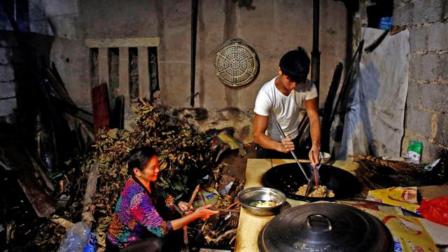 Shi Shenwei y su abuela, preparan el desayuno en la cocina en una casa antigua, que sirve como dormitorio para los trabajadores de una construcción cercana a un templo budista en el pueblo de Huangshan, cerca de Quanzhou,China