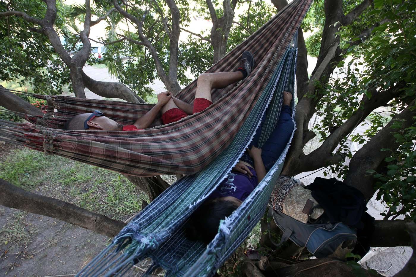 """ACOMPAÑA CRÓNICA: BRASIL VENEZUELA BRA07. BOA VISTA (BRASIL), 22/10/2016.- Los venezolanos José Antonio Garrido (i) y Sairelis Ríos (d) duermen en sus hamacas este jueves, 20 de octubre de 2016, frente a la terminal de autobuses de Boa Vista, estado de Roraima (Brasil). Es venezolana, tiene 20 años, quiere ser traductora y hoy, en una hamaca colgada en un árbol que ha convertido en su casa en la ciudad brasileña de Boa Vista, mece unos sueños que, según aseguró, no serán truncados por """"el fracaso de una revolución"""". """"No estoy aquí por política. Lo que me trajo aquí fue el fracaso de unas políticas"""", dijo a Efe Sairelis Ríos, quien junto a su madre Keila y una decena de venezolanos vive en plena calle, frente a la terminal de autobuses de Boa Vista, una ciudad que en los últimos meses ha recibido unos 2.500 emigrantes de ese país vecino. EFE/Marcelo Sayão"""