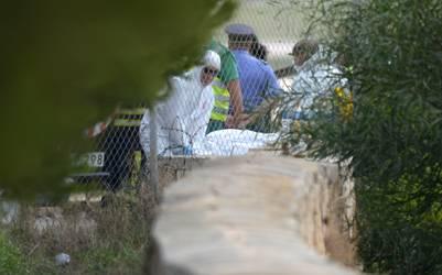 El cuerpo de una de las víctimas del accidente aéreo en Malta es retirado del lugar por forenses. / AFP