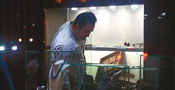 El dueño del negocio observa las vitrinas de donde fueron sustraídas joyas de oro. El negocio tiene seguro