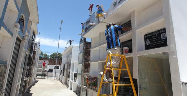Los albañiles aumentan sus ingresos pintando tumbas y mausoleos, como en el cementerio Hamacas