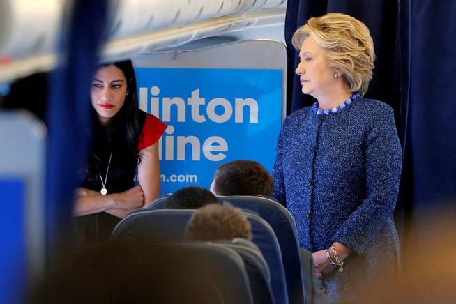 Hillary Clinton habla con su equipo, incluida Huma Abedin, durante un trayecto de campaña en avión. (Reuters)