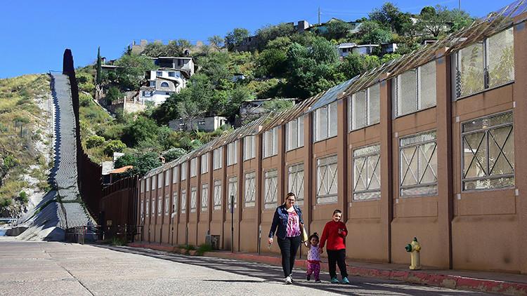 Una mujer y dos niños camina junto al muro que separa EE.UU. y México, 11 de octubre de 2016