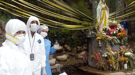 Personal de saludo toma muestras del agua de la vertiente en la Gruta de Lourdes. Foto: Ministerio de Gobierno