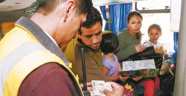 Funcionarios revisan la identificación de los pasajeros antes de que el bus salga de la terminal