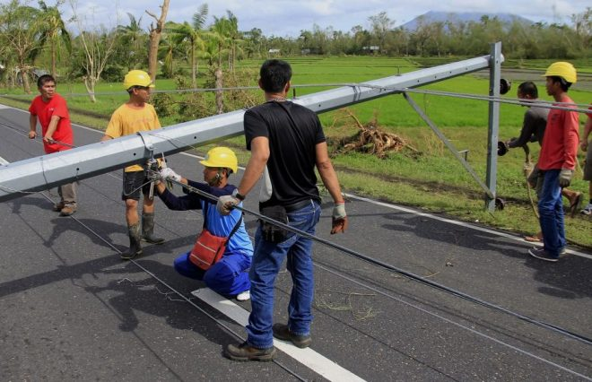Workers check downed electric posts on the national road after typhoon Nock-Ten made landfall in Nabua, Camarines Sur on December 26, 2016. Typhoon Nock-Ten, which made landfall on the eastern island province of Catanduanes on December 25, is forecast to move westward towards the country