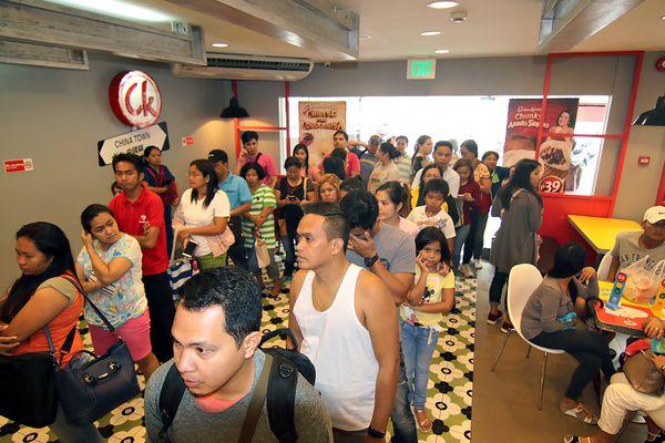 Decenas de personas hacen fila en un restaurante de comida rápida. (AFP PHOTO)