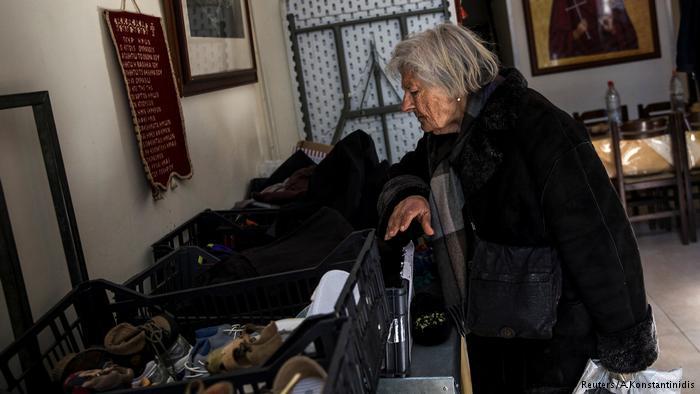 Pobreza en Grecia: una mujer busca vestimenta de donaciones.