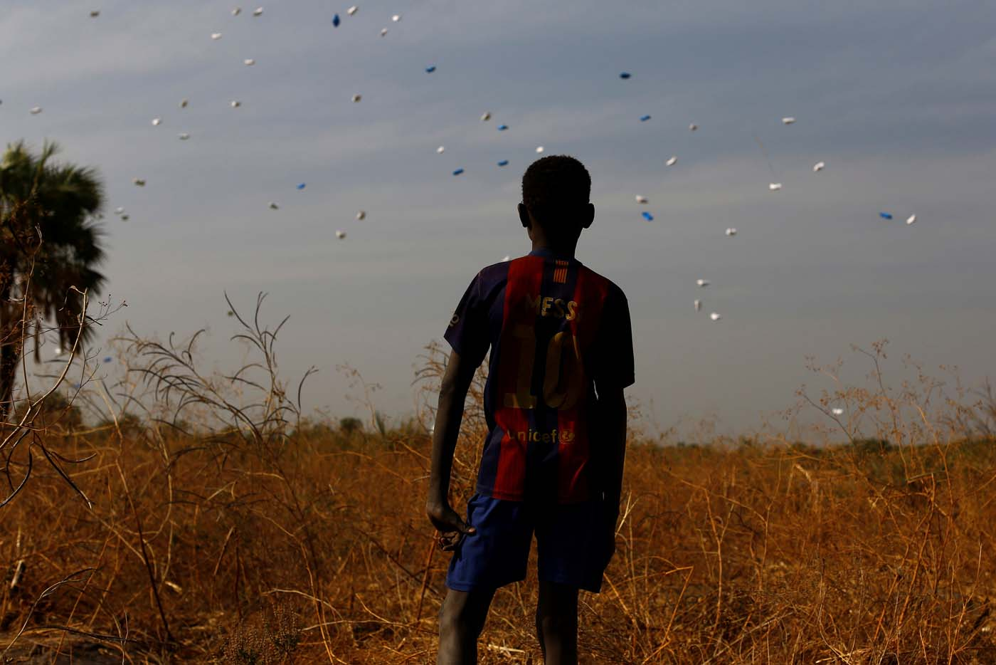 A boy watches sacks of food drop to the ground during a United Nations World Food Programme (WFP) airdrop close to Rubkuai village in Unity State, northern South Sudan, February 18, 2017. Picture taken February 18, 2017. REUTERS/Siegfried Modola