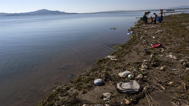 La basura cubre la costa del lago Titicaca, donde la activista ambiental Maruja Inquilla habla con los habitantes de Coata, en la región de Puno, Perú