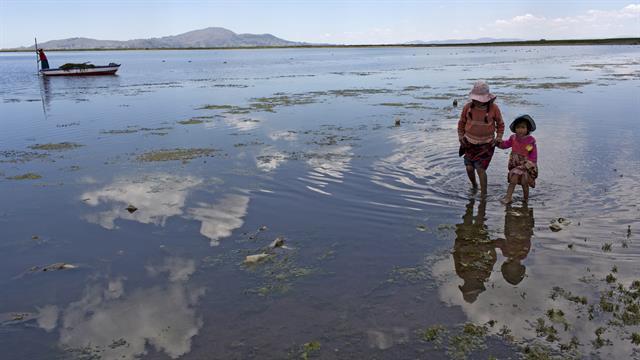 Primos de la familia Avila buscan juguetes desechados en las orillas del Lago Titicaca, en Coata, en la región de Puno, Perú.