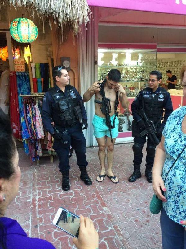 En las imágenes se puede ver al turista colocándose el rifle, que aparenta ser de la familia del M16 estadounidense, en medio de los dos policías, para luego posar alegremente ante las cámaras