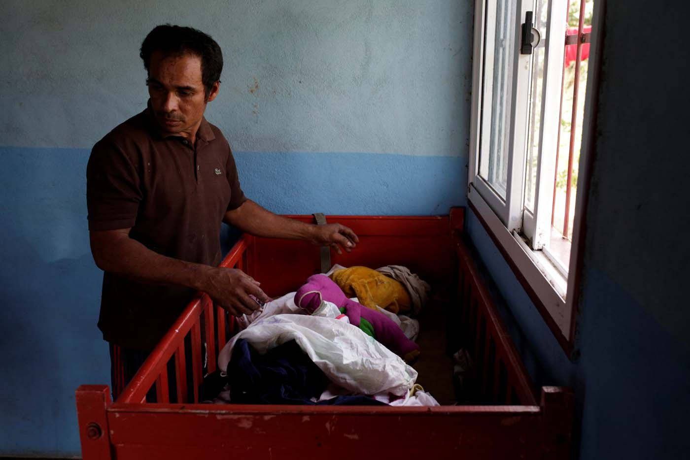 Tulio Medina, father of Eliannys Vivas, who died from diphtheria, puts clothes on a cot at his home in Pariaguan, Venezuela January 26, 2017. Picture taken January 26, 2017. REUTERS/Marco Bello