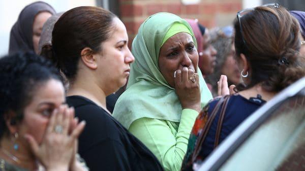El llanto de una mujer mientras espera datos de sus seres queridos al pie de la torre Grenfell (Reuters)
