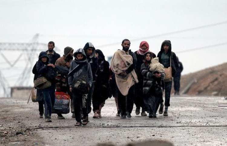 Iraquíes desplazados caminan bajo la lluvia (Reuters)