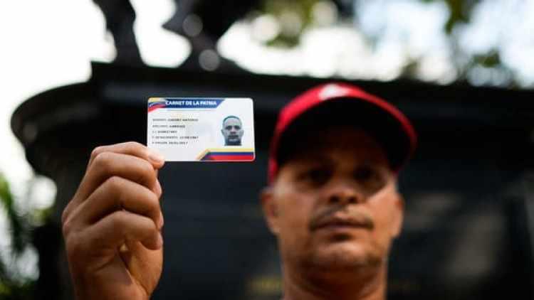 Un hombre muestra el Carnet de la Patria, que permite adquirir alimentos subsidiados (AFP/archivo)