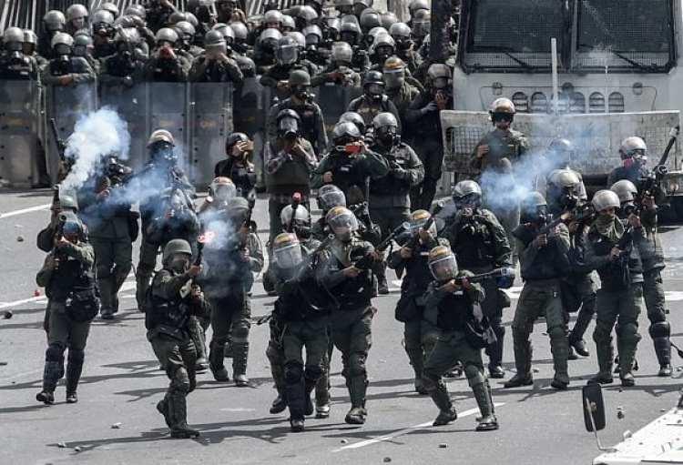 Miembros de la Guardia Nacional Bolivariana reprimen a la oposición en Caracas (AFP)