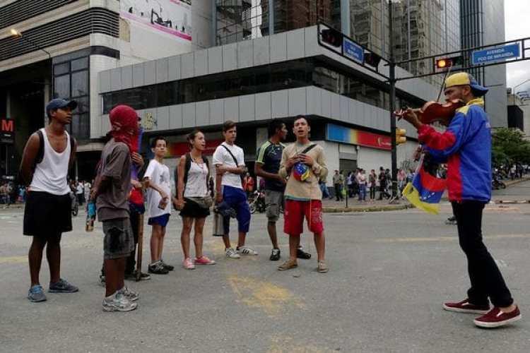 El músico ante una manifestantes opositoras en las calles de Caracas. (REUTERS/Carlos Garcia Rawlins)