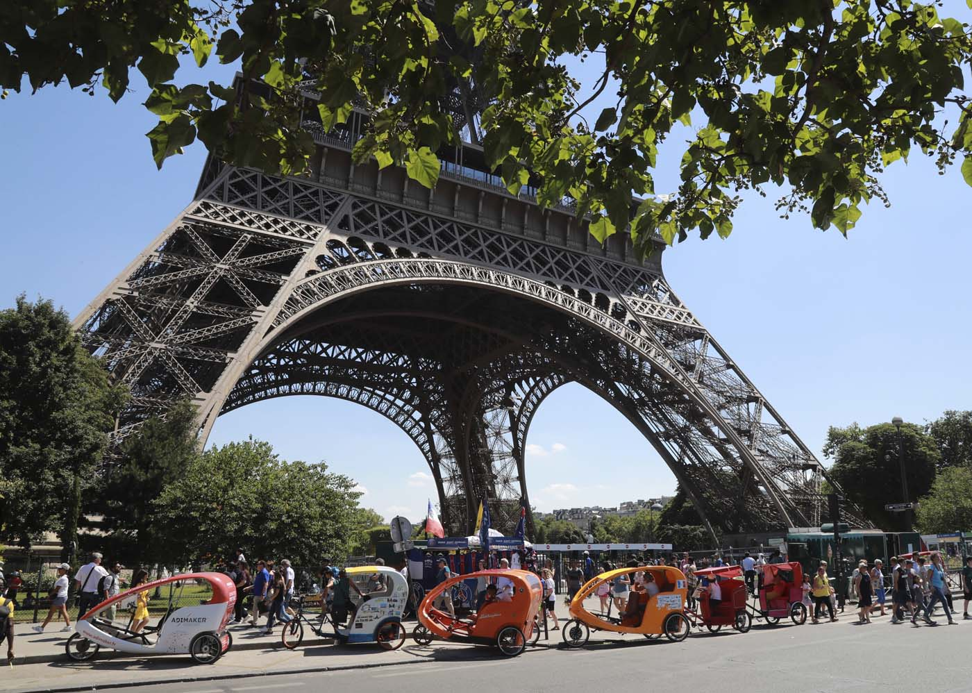 (FILES) This file photo taken on July 07, 2017 shows Pedicab drivers waiting for clients near the Eiffel Tower in Paris. After a decline in 2016 due to the terror attacks in Paris and Nice, tourism in Paris and Ile de France is in much better shape in the first half of 2017, with 1,5 million tourists and 3,3 million overnight stays more than a year ago. / AFP PHOTO / JACQUES DEMARTHON