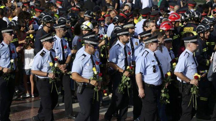 Varios policías llevanflores en honor a la víctimas del ataque terrorista mientras participan de la manifestación (AP)