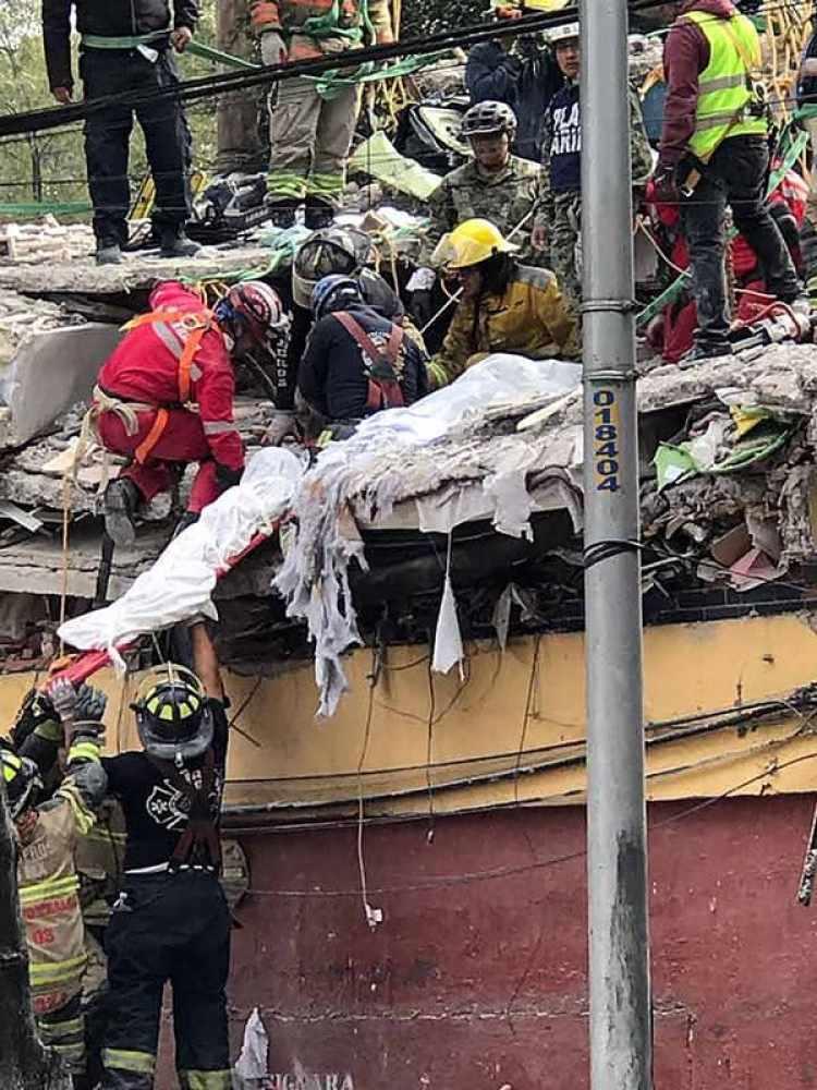 Rescatistas remueven los restos de los hermanos Astudillo de entre los escombros