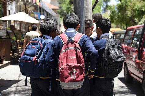 Estudiantes caminan con sus útiles escolares por el centro de la ciudad.