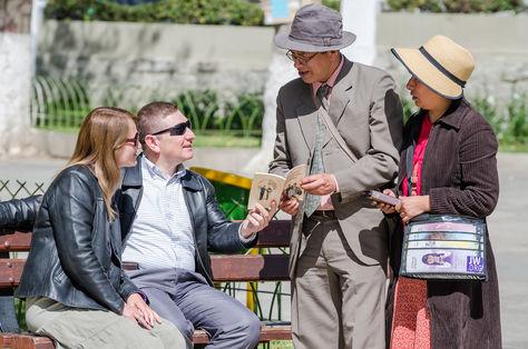 A la derecha, un par de testigos de Jehová predica en una de las calles de La Paz.