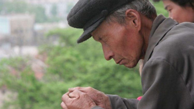 Un hombre norcoreano rezando.